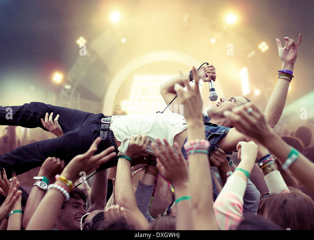 Performer crowd surfing at music festival - Stock-Bilder
