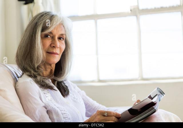 Portrait of attractive senior woman reading magazine - Stock Image