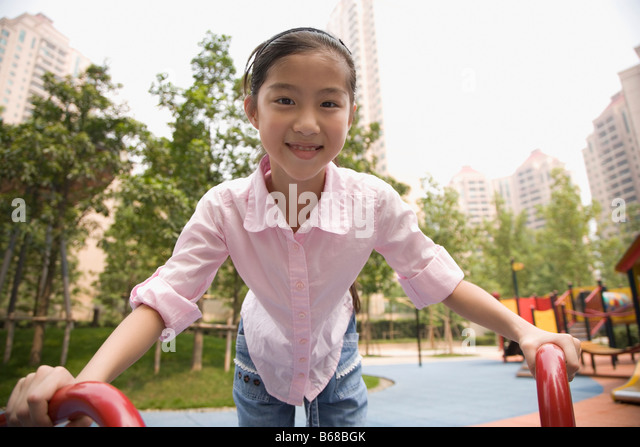 Portrait of a girl playing on a merry-go-round and smiling - Stock-Bilder