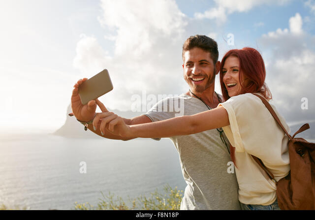 Laughing young couple on holidays making selfie with mobile phone. Young couple by the bay taking a selfie portrait - Stock Image