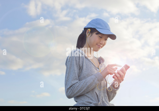 Young female runner choosing music from MP3player - Stock Image