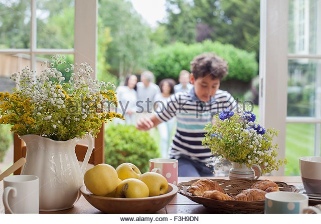 Family coming in for breakfast after walk in garden - Stock Image