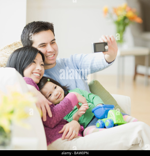 Family on couch posing for photograph - Stock Image