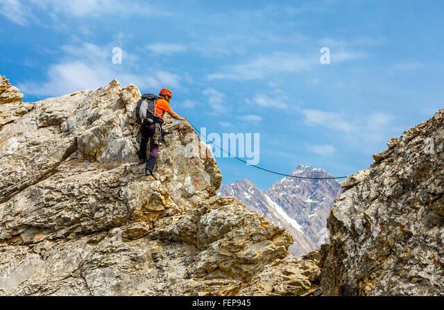 Brave man climbs rocky ridge - Stock Image