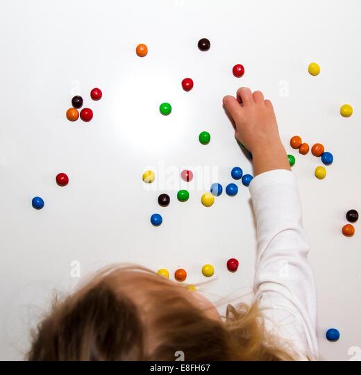 Girl eating chocolate candies - Stock Image