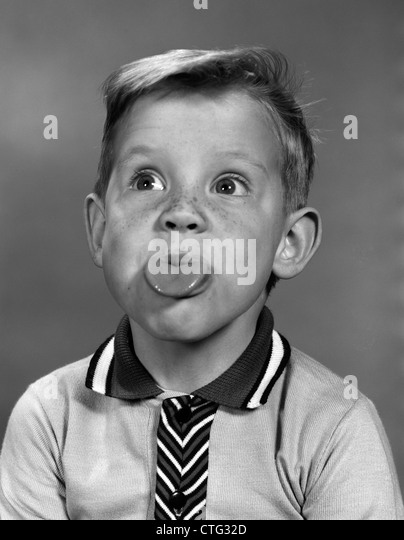 1960s PORTRAIT BOY WITH BLOND HAIR & FRECKLES STICKING TONGUE OUT - Stock Image