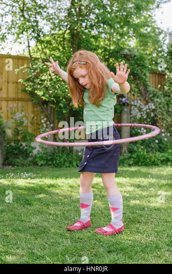 Little girl playing with a hula hoop in her garden - Stock Image