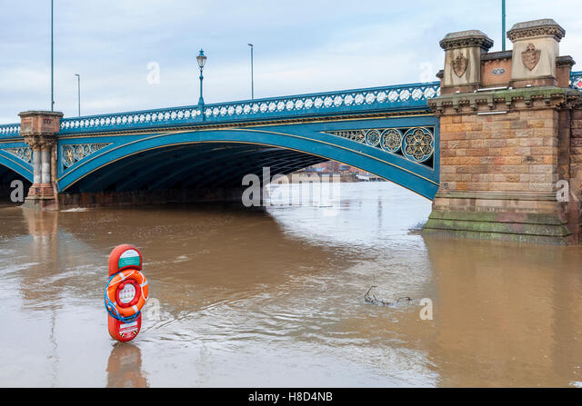 Lifebuoy standing in flood water as the River Trent overflows the riverbank at Trent Bridge, Nottingham, England, - Stock Image