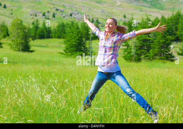 Happy girl jumping on the field, enjoying fresh air and spring green grass, freedom and happiness concept - Stock Image