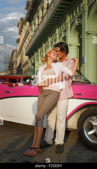 Young couple leaning against vintage convertible, Havana, Cuba - Stock Image