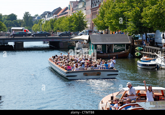Canal cruise boats in the Christianshavns Canal in Copenhagen. View towards the streets Torvegade and Oven Gaden - Stock Image