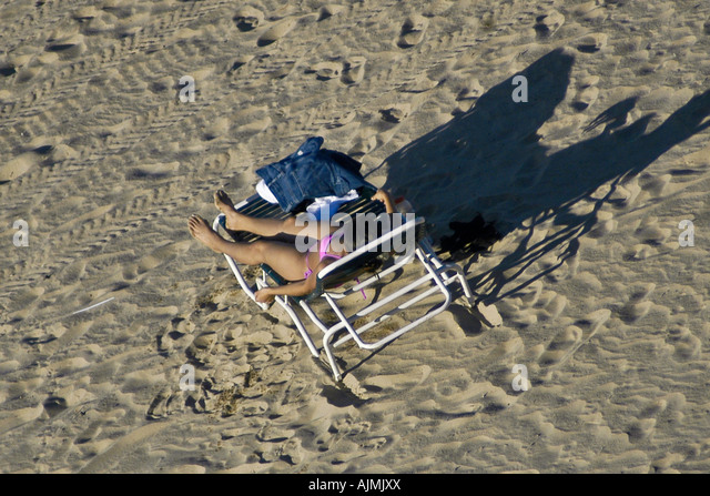 San Juan Puerto Rico Isla Verde beach, with woman sunbather on lounge chair, aerial view - Stock Image