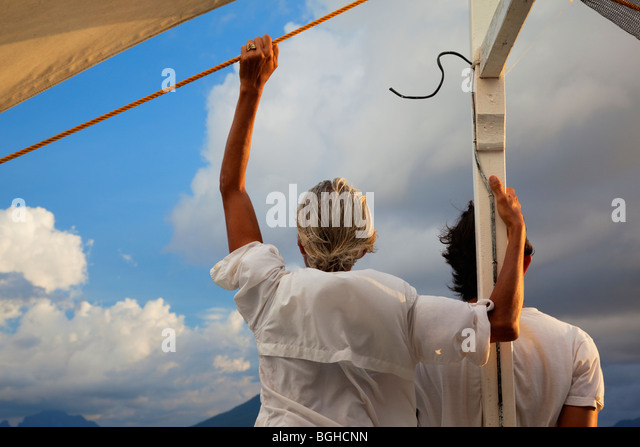 Two people looking towards the horizon from the front of a boat; Palawan; Philippines. - Stock Image