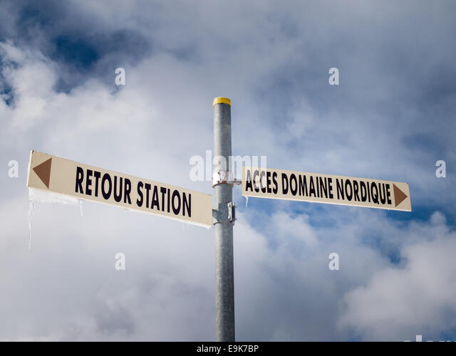 signpost giving direction to nordic and alpine skiing areas in french with cloudy blue sky behind - Stock Image