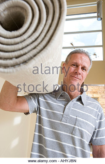 Senior man carrying rolled-up carpet on shoulder, moving house, smiling, low angle view, front view, portrait - Stock-Bilder