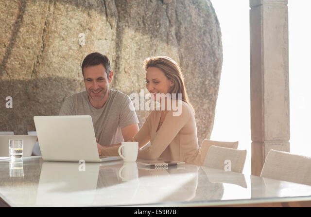 Couple using laptop at breakfast - Stock-Bilder