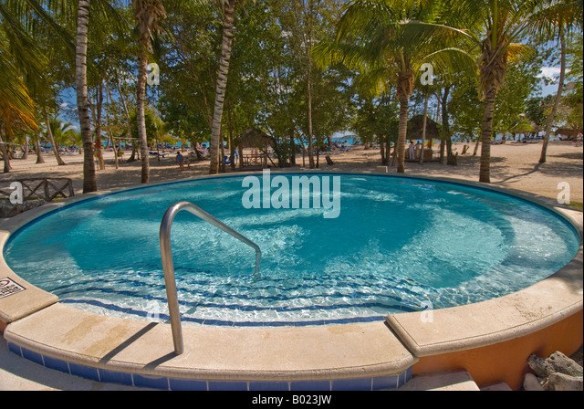 Dominican Republic Bayahibe small round swimming pool palm trees beach blue sky warm weather tropical vacation holidays - Stock Image