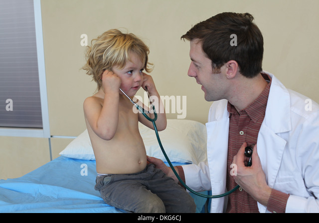 Young male doctor in clinic sharing stethoscope with boy - Stock Image