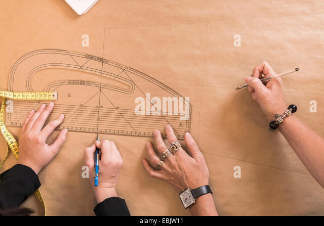 Overhead view of seamstresses hands drawing with curved ruler on dressmakers pattern in workshop - Stock-Bilder