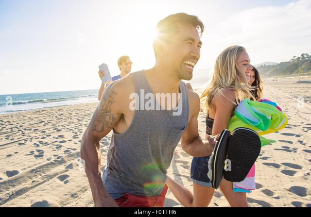 Group of friends walking on beach, laughing - Stock Image