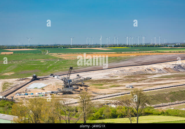 A refilled lignite pit mine in front of a large wind turbine park showing the change from fossil fuels to renewable - Stock Image