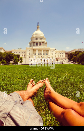 USA, Washington D.C., Couple relaxing in meadow in front of the Capitol - Stock Image