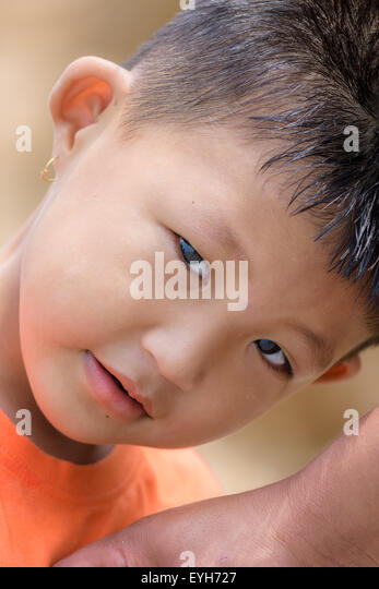 Portrait of a little mongoloid boy happy and innocent with copy space, curious look in the eyes - Stock Image