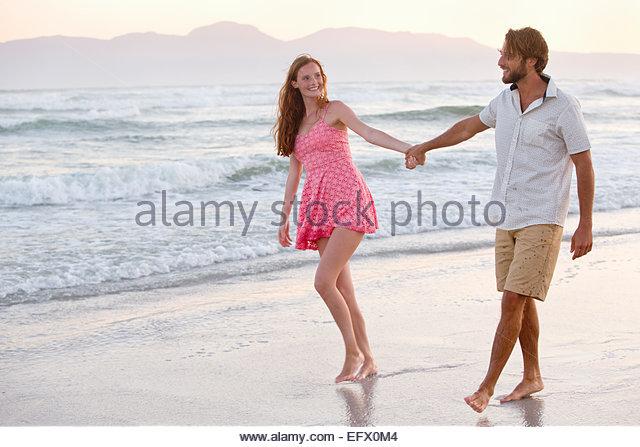 Couple, holding hands, walking on sunny beach - Stock-Bilder