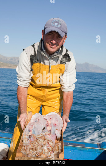 fisherman on boat, presenting the fish - Stock Image