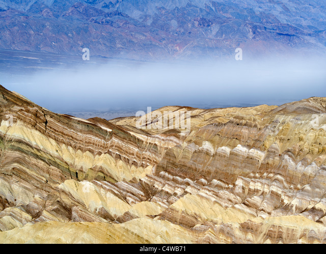 Colorful rock formations and dust storm as seen from Golden Canyon Trail. Death Valley National Park, California - Stock Image