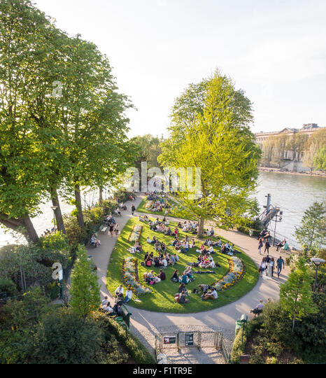 Park at the tip in the Seine . Tourists and locals enjoy the evening sunshine at the tip of the Île de la Cité - Stock Image