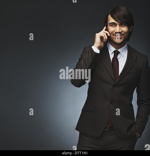 Asian man talking on mobile phone. Handsome young mixed race man on black background. Professional young businessman - Stock Image