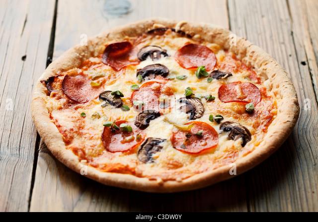 pepperoni and mushrooom pizza on rustic table - Stock Image