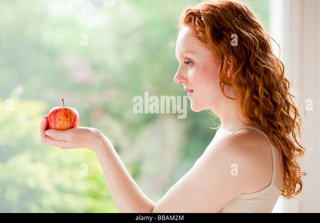 Girl holding apple - Stock Image