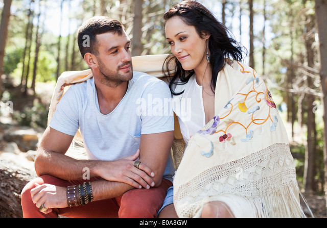 Young couple sitting in forest, arm around - Stock-Bilder