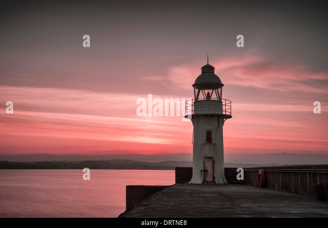 Lighthouse and breakwater in the coastal fishing port of Brixham South Devon taken at sunset. - Stock Image