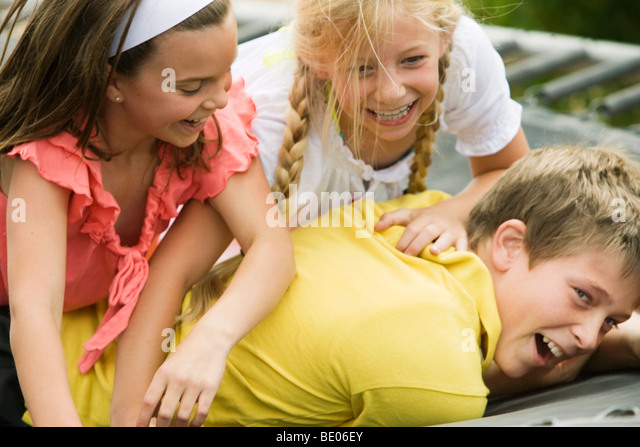 2 young girls wrestling with young boy - Stock Image