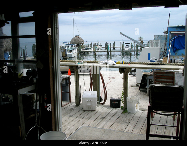 Inside view from an angler's shop to jetties and boats - Stock Image