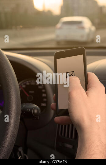 Checking e-mail while driving - Stock-Bilder