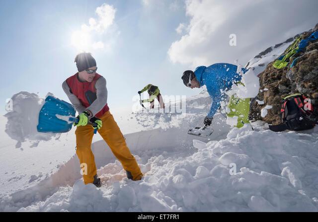 Men shovelling snow for bivouac camp, Tyrol, Austria - Stock Image