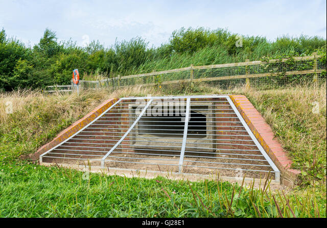 Water overflow outlet from a lake into a balancing lake or flood basin. - Stock Image