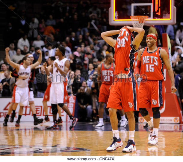 New Jersey Nets guard Devin Harris (34) covers his head with his jersey in front of guard Vince Carter (15) as Toronto - Stock Image