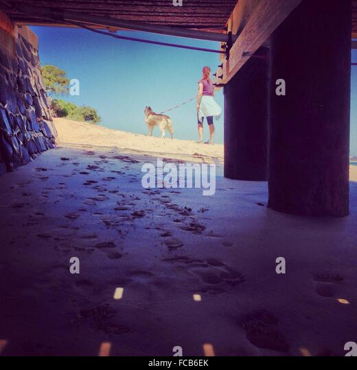 Woman With Dog At Beach Seen From Underneath Of Pier - Stock Image