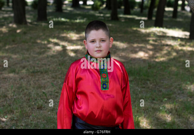 the boy in the Russian shirt against the wood - Stock-Bilder