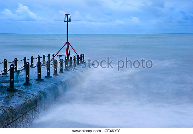 Waves breaking around a red beacon at the end of a breakwater. - Stock-Bilder