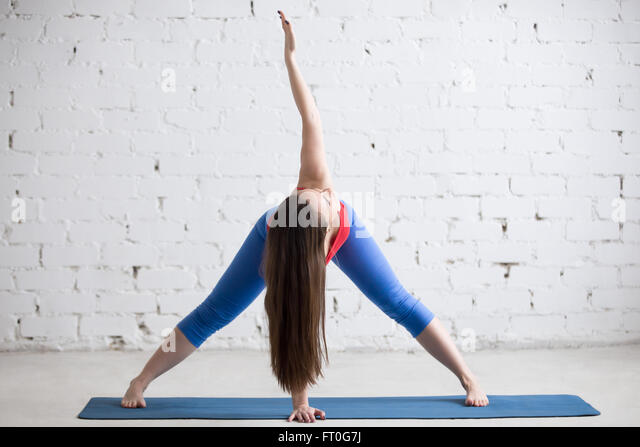 Beautiful young woman in bright colorful sportswear working out indoors in loft interior on blue mat - Stock-Bilder