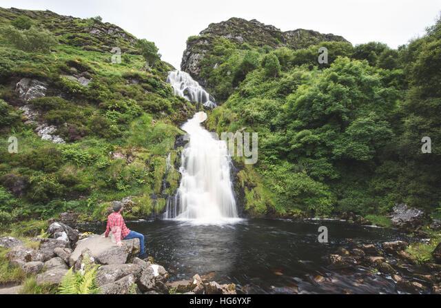 Lone walker at Assarancagh Waterfall, Adara.  County Donegal, Ireland / Assarnacally Waterfall - Stock-Bilder