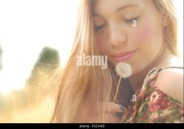 beautiful blonde on the outside with dandelion girl with beautiful skin and face beautiful girl in love - Stock Image
