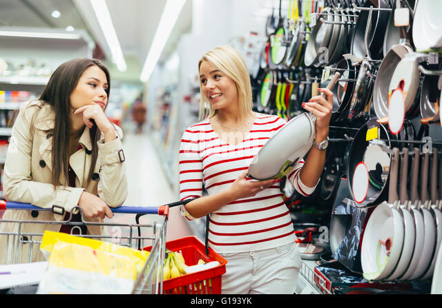 Women shopping cookware in supermarket - Stock Image