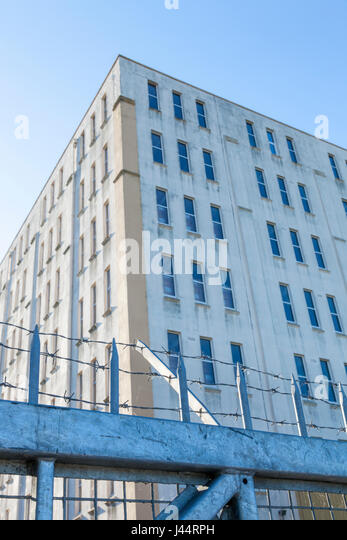 Security fencing around a factory building - Stock Image